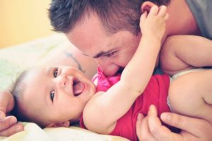 Man cuddling smiling baby on a blanket. Sleep tips for baby.