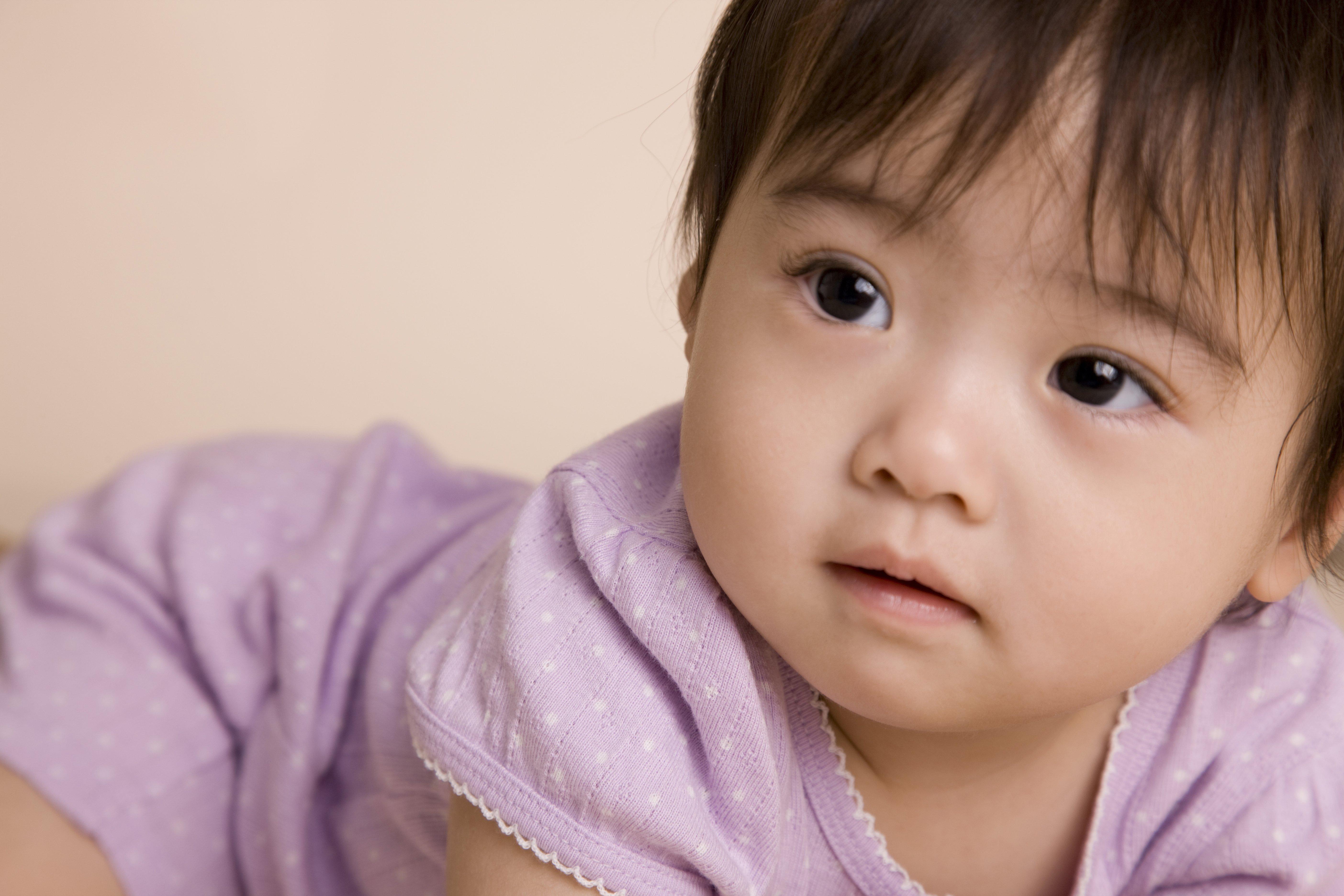 Closeup of baby in purple onesie.