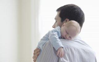 Man holding sleeping baby.